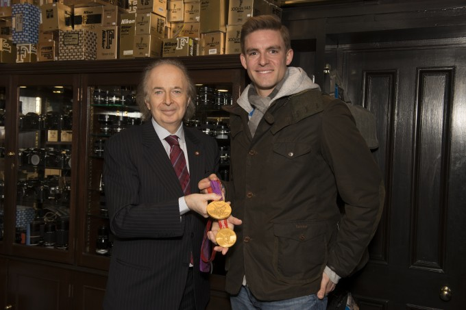 Olympic Gold Medalist Pete Reed MBE (right) in the second-hand department of Grays of Westminster with Gray Levett holding Pete's two gold medals.
